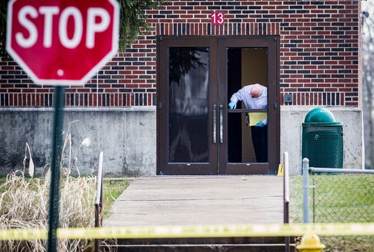 Investigators examine a shattered glass door at Dennis Intermediate School where police say an alleged school shooter made entrance Thursday morning.