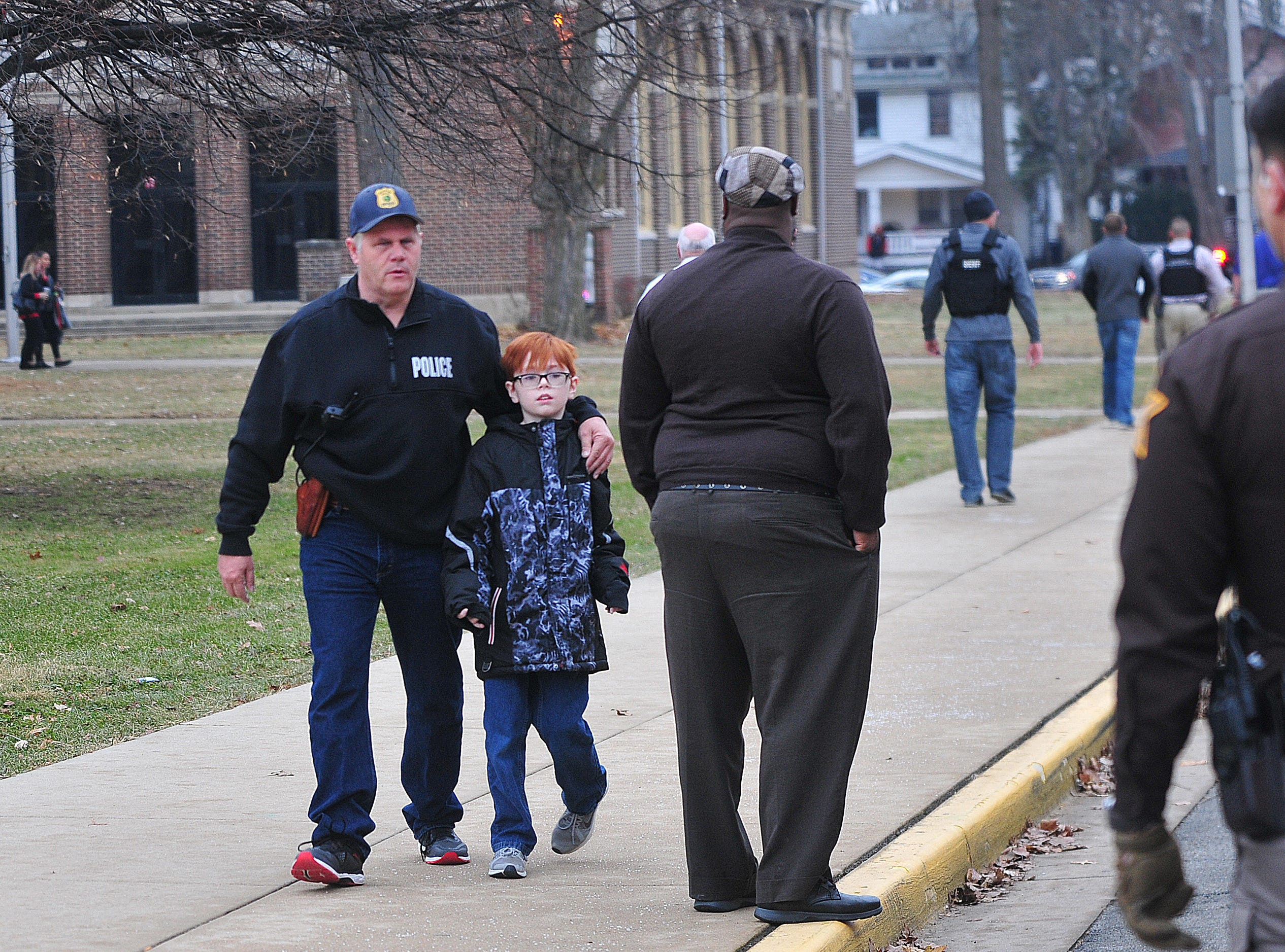 Police escort students out of Dennis Intermediate School after police exchanged gunfire with a suspect near Dennis on Thursday morning. The suspect was confirmed as the only fatality.