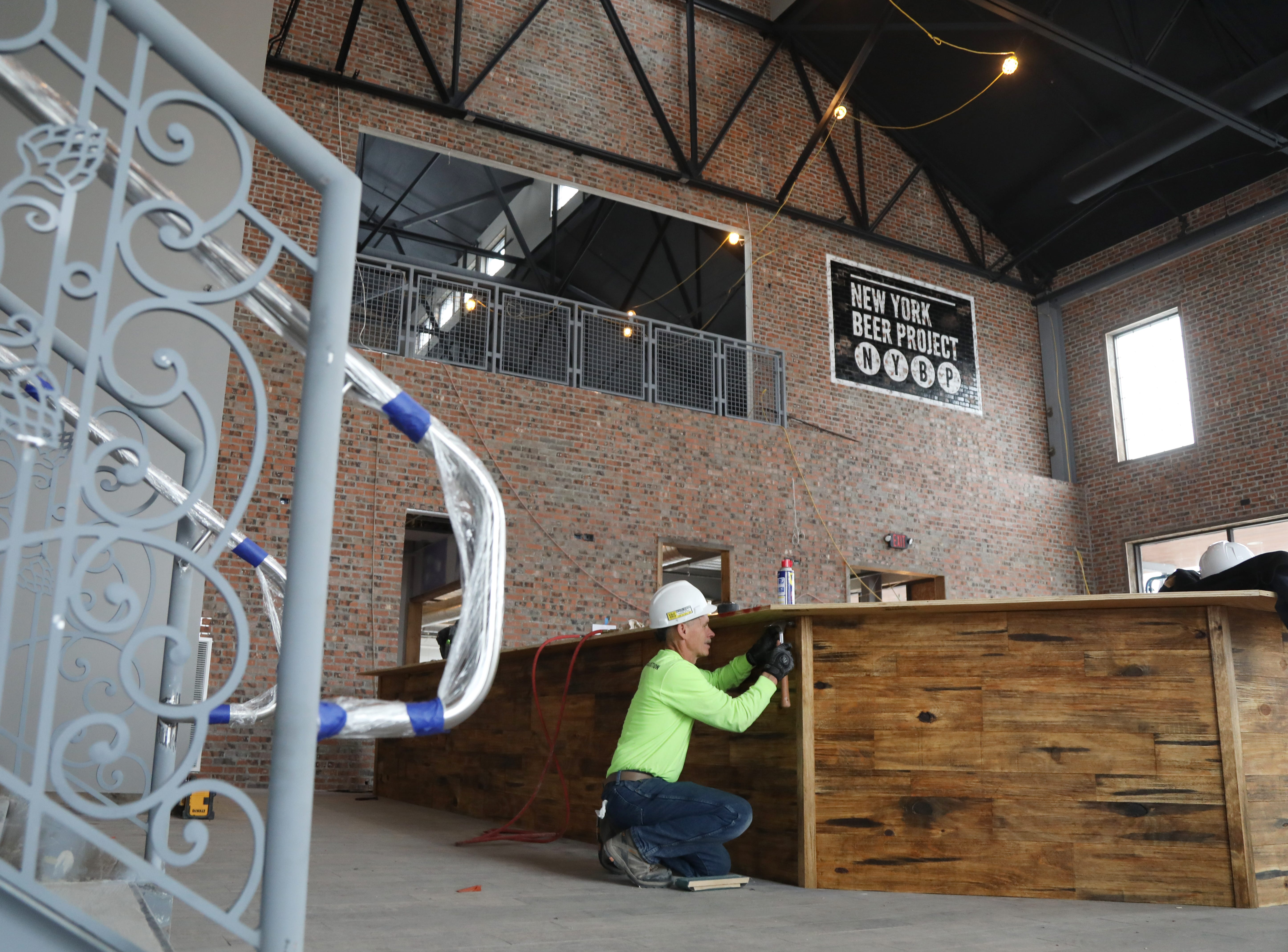 Finish work on the outside of the bar in the tap room at New York Beer Project in Victor.