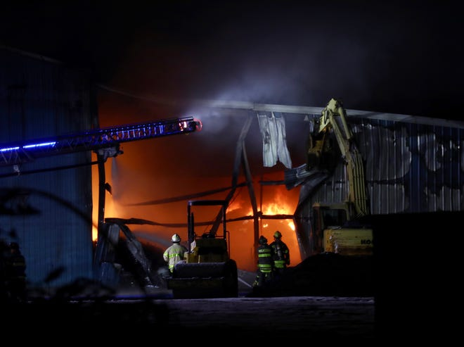 An excavator creates a larger opening for firefighters to attack the fire.