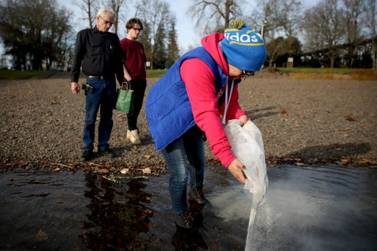Carolina Johnson, a manager at a West Salem Subway, spreads the ashes of Don Blocker as his brother, Richard Blocker, 61, and great-nephew, Darrick Blocker, 20, both of Vancouver, Wash., look on at Wallace Marine Park in West Salem on Thursday, Dec. 13, 2018. Blocker lived in the park for about 40 years. He died the day after Thanksgiving, unable to get warm after falling into a pond near his tent. Johnson became friends with him when she used to give him her employee meals at Subway.