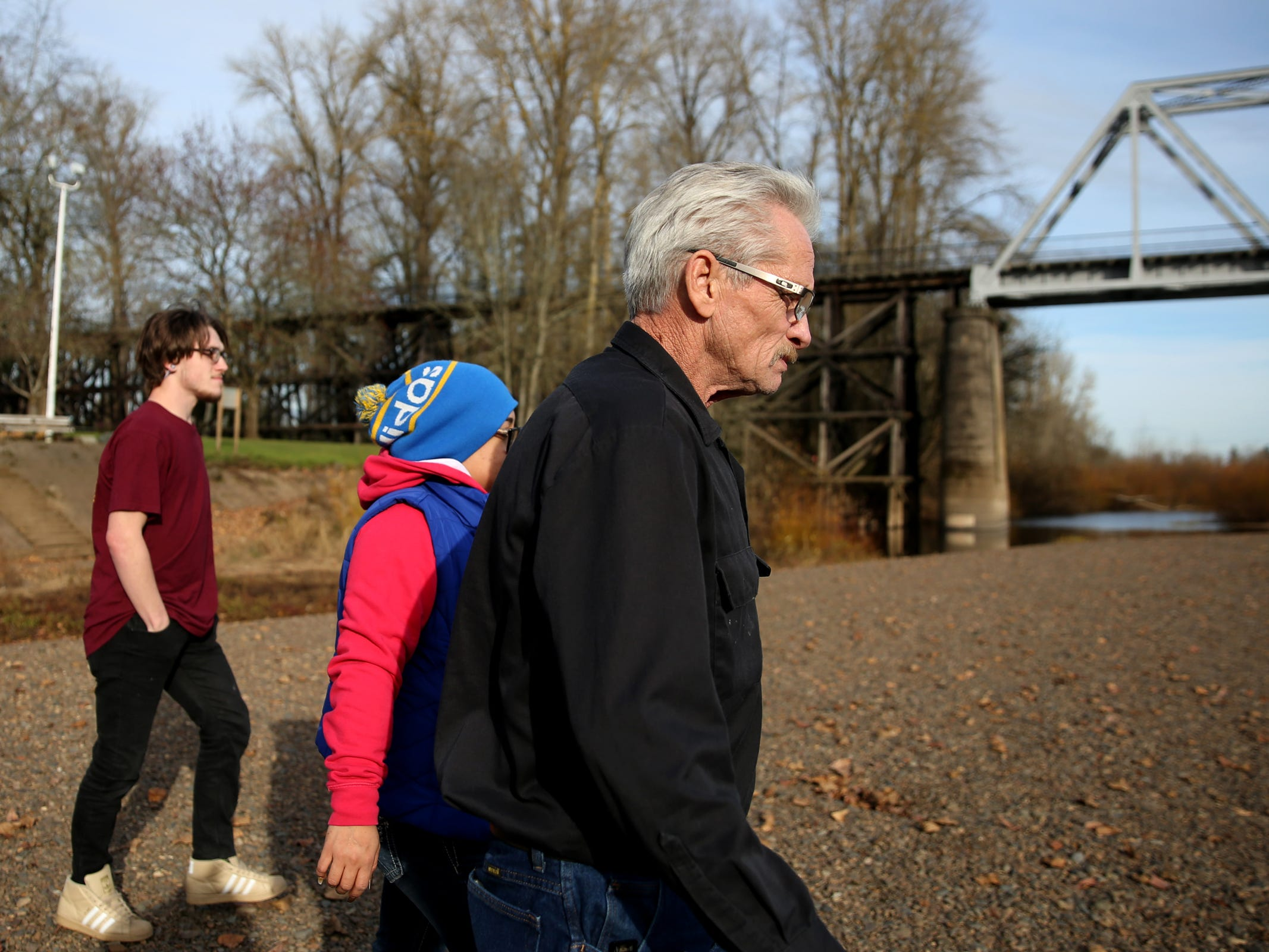 Richard Blocker, 61, of Vancouver, Wash., Carolina Johnson, a manager at a West Salem Subway, and Darrick Blocker, 20, of Vancouver, Wash., walk to spread the ashes of Richard Blockers' brother, Don Blocker, in the Willamette River at Wallace Marine Park in West Salem on Thursday, Dec. 13, 2018. Blocker lived in the park for about 40 years. He died the day after Thanksgiving, unable to get warm after falling into a pond near his tent.