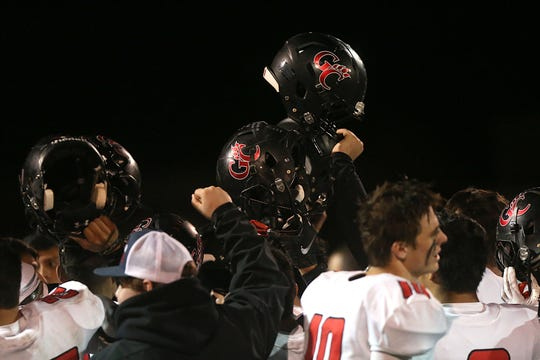 The Garden City Bearkats hold up their helmets in celebration after a win.