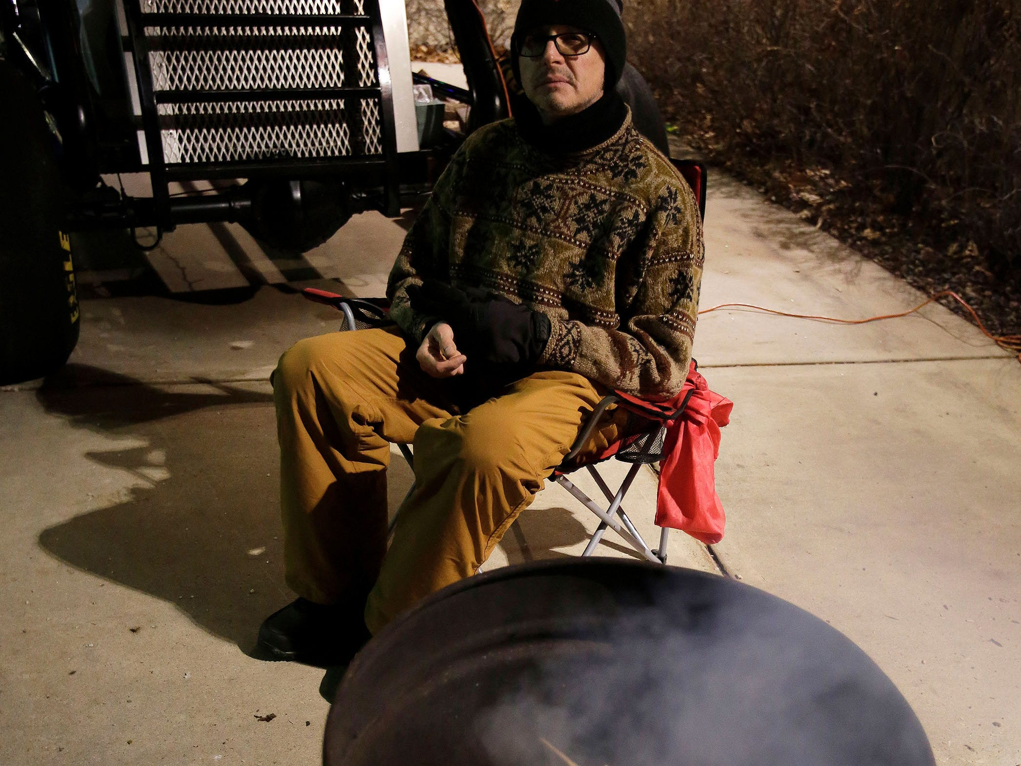 Salvation Army Captain Daryl Mangeri sits by a small fire he built in a barrel out side of Festival Foods, Wednesday, December 12, 2018, in Sheboygan, Wis. Mangeri is participating in Freezing for a Reason, which he says is to shine a light on the fact that there are homeless that live among us.