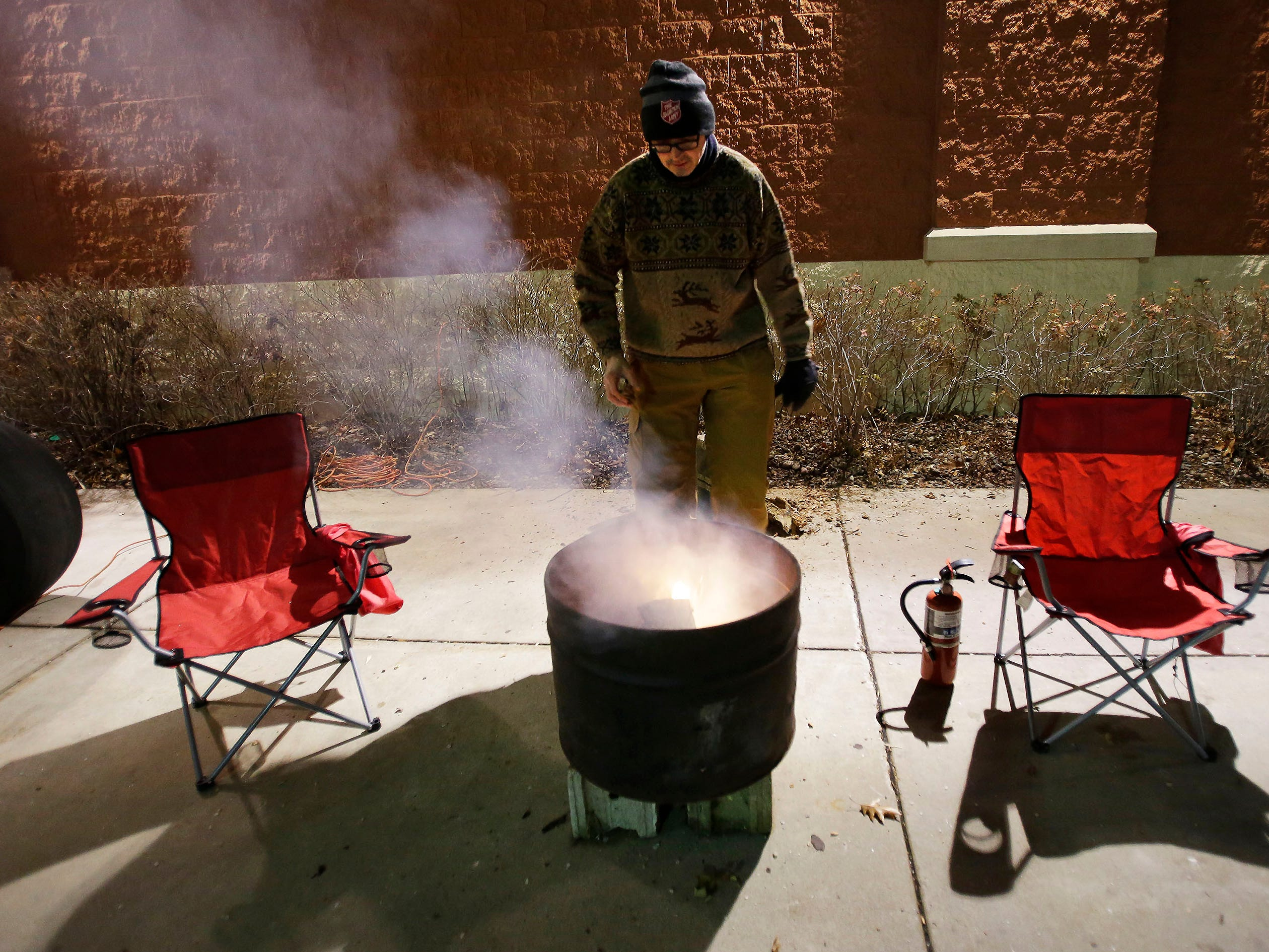 Salvation Army Captain Daryl Mangeri stands by a small fire he built in a barrel out side of Festival Foods, Wednesday, December 12, 2018, in Sheboygan, Wis. Mangeri is participating in Freezing for a Reason, which he says is to shine a light on the fact that there are homeless that live among us.