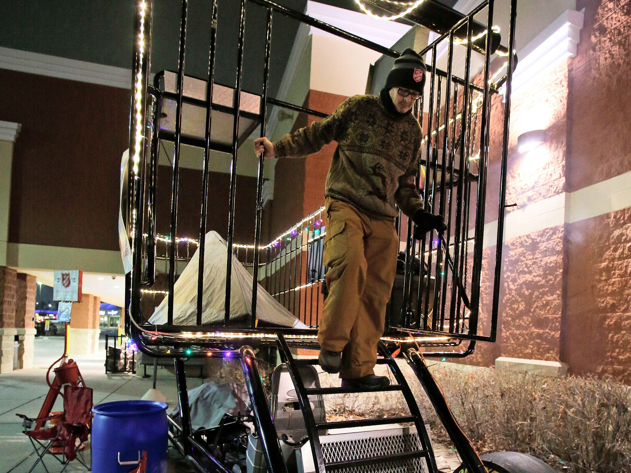 Salvation Army Captain Daryl Mangeri steps down from the giant shopping cart at Festival Foods, Wednesday, December 12, 2018, in Sheboygan, Wis. Mangeri is participating in Freezing for a Reason, which he says is to shine a light on the fact that there are homeless that live among us. He is sleeping overnight outside in a tent on the shopping cart, which he says is a symbol of the homeless in many cities.