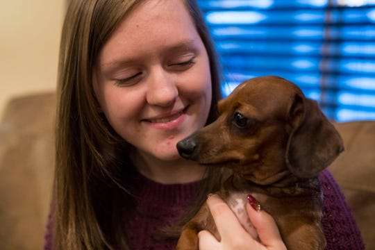 Kayla Nelson, 20, holds the family dog at their house in Sioux Falls, S.D., Wednesday, Dec. 12, 2018. Kayla has a rare (1 in 500) medical condition called Cerebral Cavernous Malformation (CCM), which is where there are tangles of blood vessels in the brain or spinal cord that will bleed and can cause hemorrhages, seizures, or stroke-like symptoms.