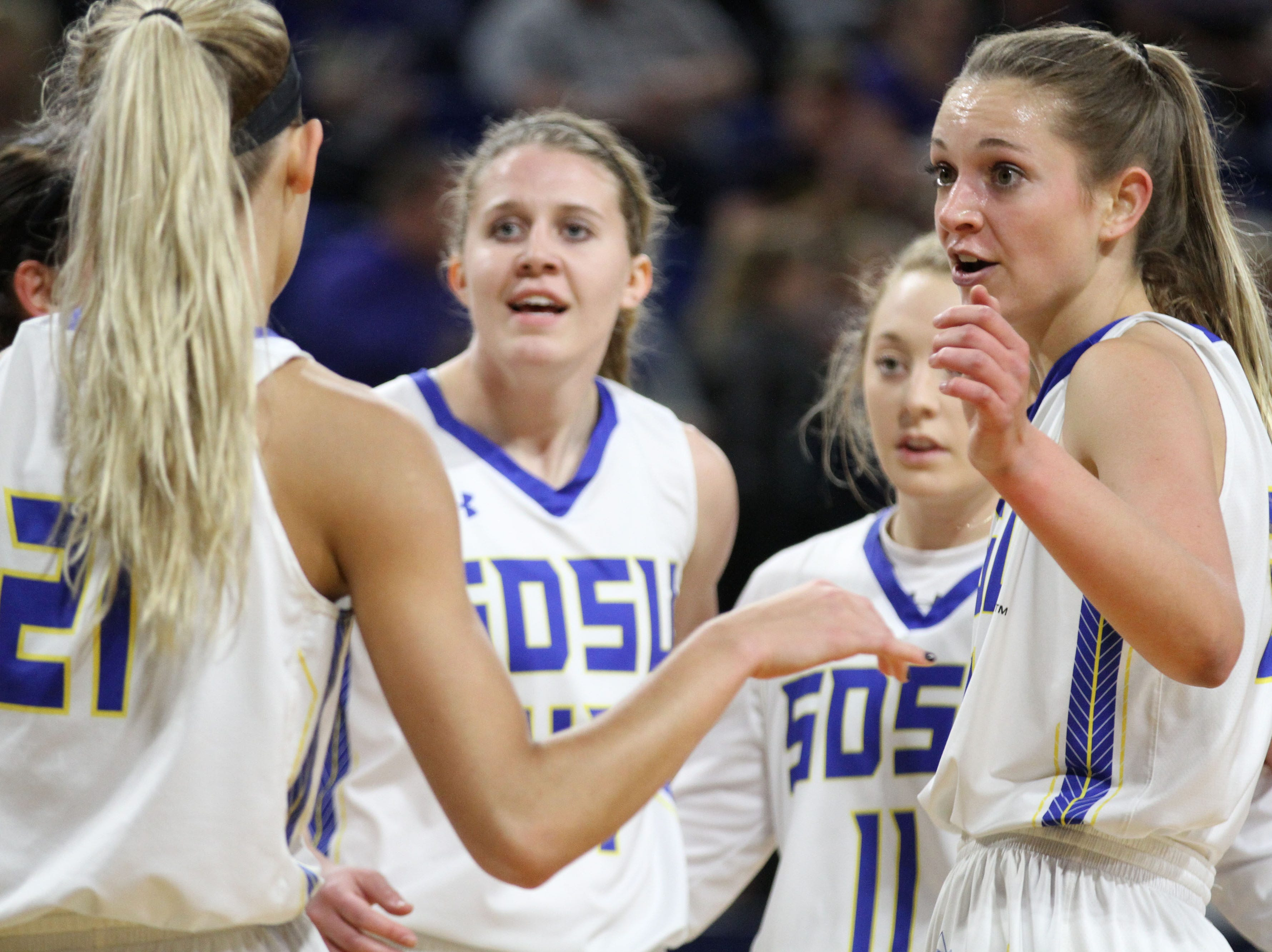 SDSU's Tagyn Larson (right) talks strategy with Tylee Irwin (21) before a free throw attempt during the first quarter of the matchup against the Ducks Wednesday night at Frost Arena in Brookings.