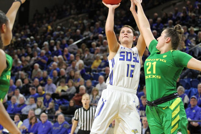 SDSU's Macy Miller (12) Scores on a tough shot over Oregon's Erin Boley during the second quarter of the matchup against the Ducks Wednesday night at Frost Arena in Brookings.