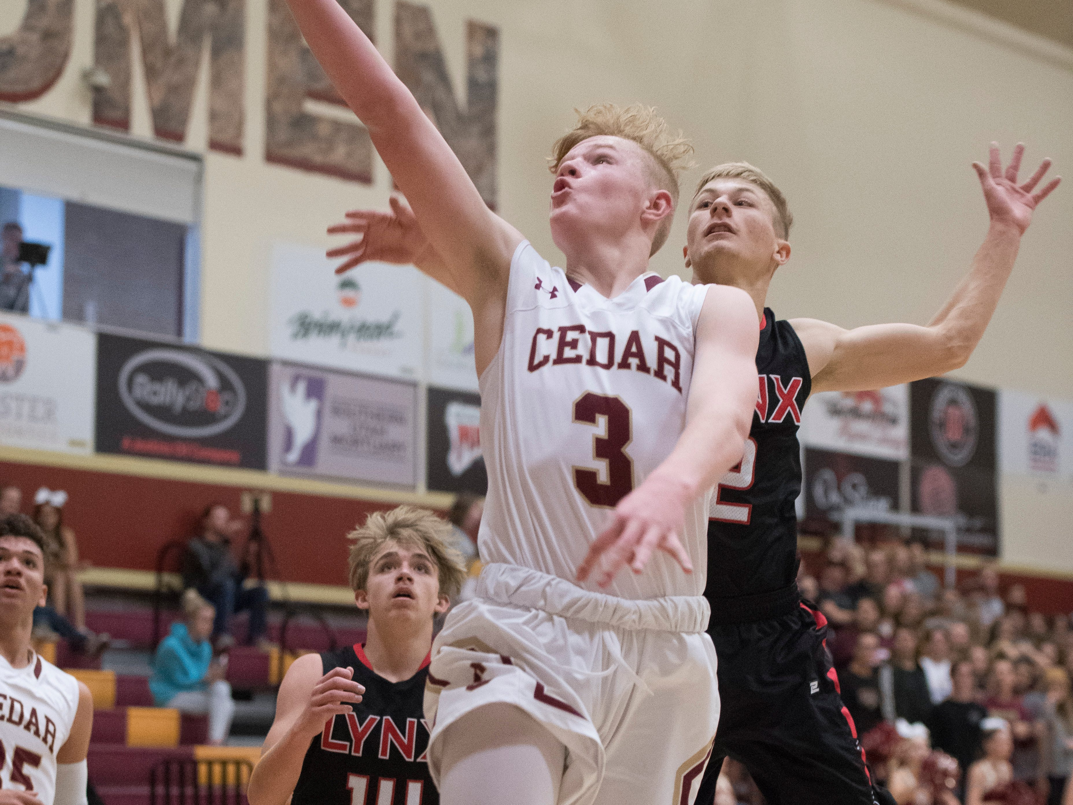 Cedar High School sophomore Gaige Savage (3) shoots a layup against Lincoln County at CHS Wednesday, December 12, 2018. The Redmen won, 80-54.