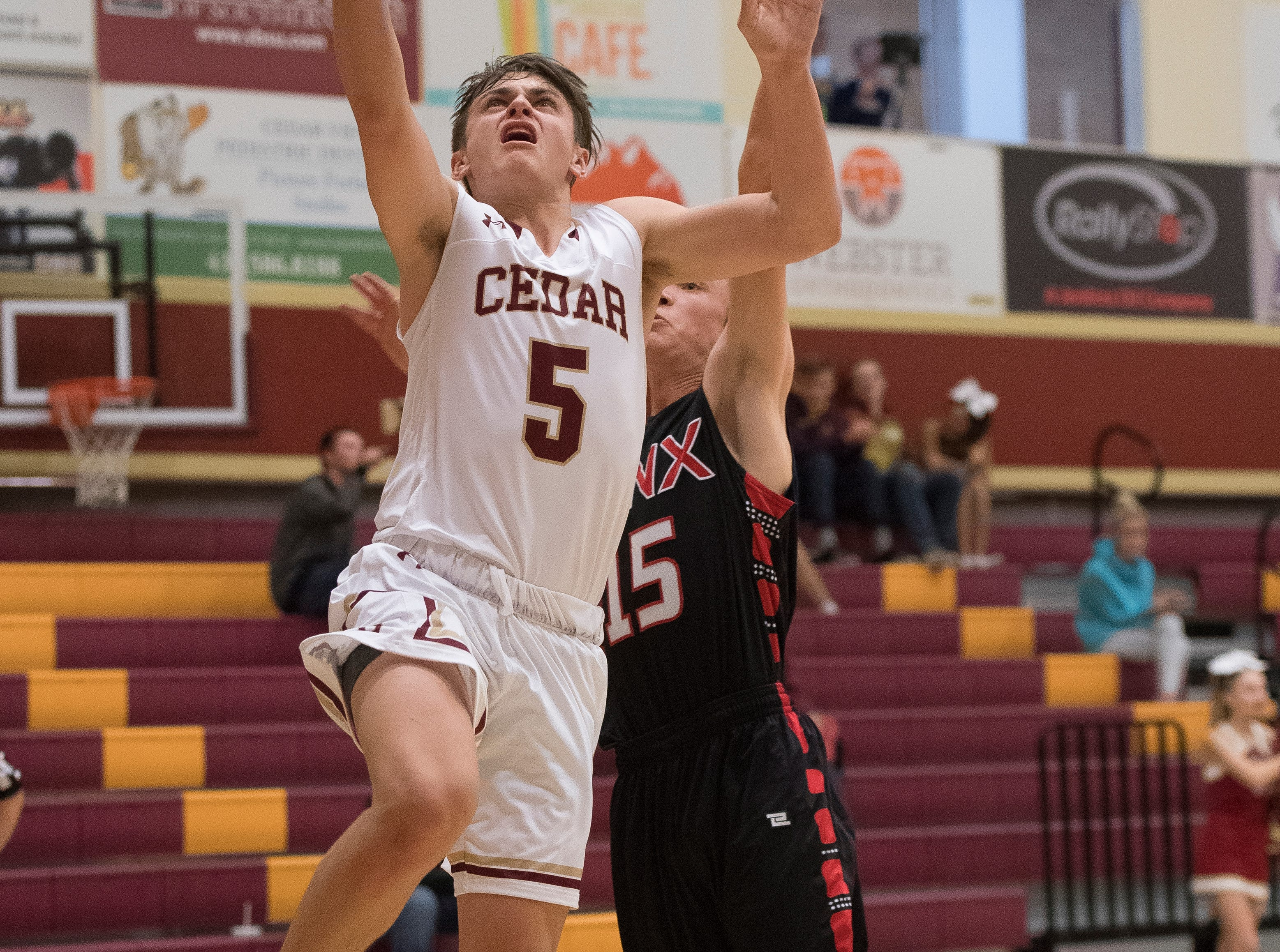 Cedar High School sophomore Treyton Tebbs (5) makes a shot against Lincoln County at CHS Wednesday, December 12, 2018. The Redmen won, 80-54.