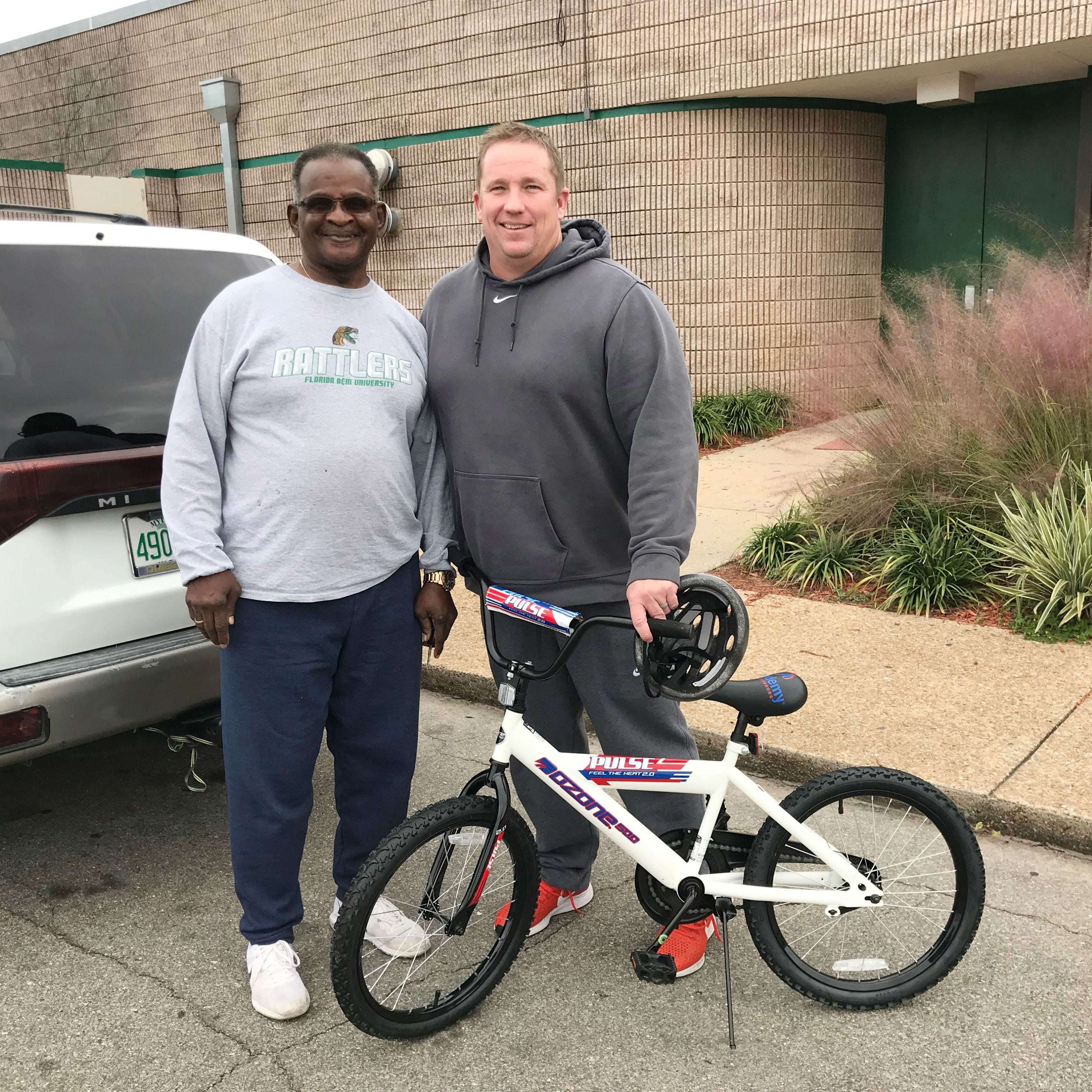 FAMU class of 1971 alum Johnny Barnes (left) donated a bike to the toy drive on Dec. 13 at the Galimore-Powell Field House. He presented the gift to linebackers coach Ryan Smith.