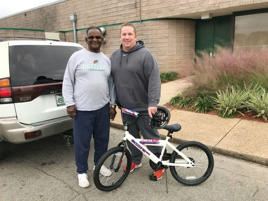 FAMU class of 1971 alum Johnny Barnes (left) donated a bike to the toy drive on Dec. 13 at the Galimore-PowellField House. He presented the gift to linebackers coach Ryan Smith.
