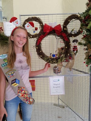 Zoe Williams of Hobe Sound Girl Scouts 30290 is pictured here with the wreath she designed and donated for the Tykes & teens Festival of Trees & Lights.
