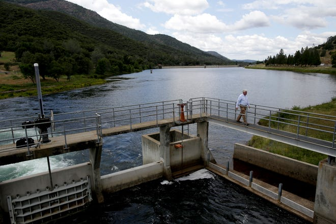 In this May 6, 2014 file photo, a utilities manager walks on a bridge over Moccasin reservoir at the Moccasin Powerhouse in Moccasin, Calif., as Tuolumne River water rushes through the plant. A state water board voyed to support a contentious proposal to boost flows through a Central California river and its tributaries, increasing habitat for salmon but delivering less water for cities and farmers. State officials say water users along the Tuolumne River have agreed to voluntary concessions that would improve salmon habitat instead of the mandated increase in water flows.