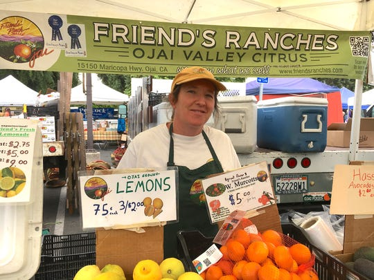 Emily Ayala of Friend's Ranches poses at the Ojai Certified Farmers' Market with lemons and other citrus. The family-owned business also sells its fresh fruit via mail order.