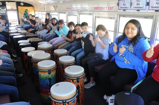 Fourth-grade teacher Claudia Medrano and her students participate in a class inside the drum bus. The hollowed-out school bus allows students to drum and work out issues while building core skills.