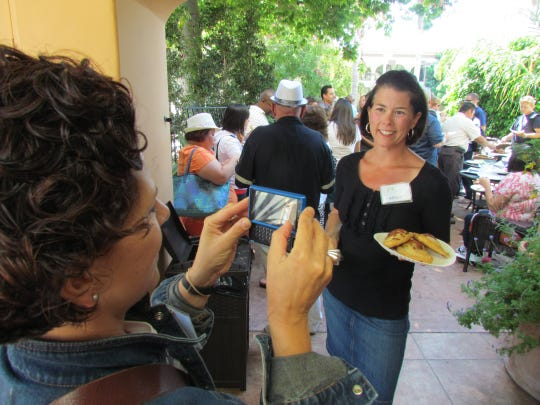 Ventura Food Tours founder Allison Costa, right, poses with a plate of savory empanadas during a tour stop at Marie Shannon Confections in downtown Ventura.