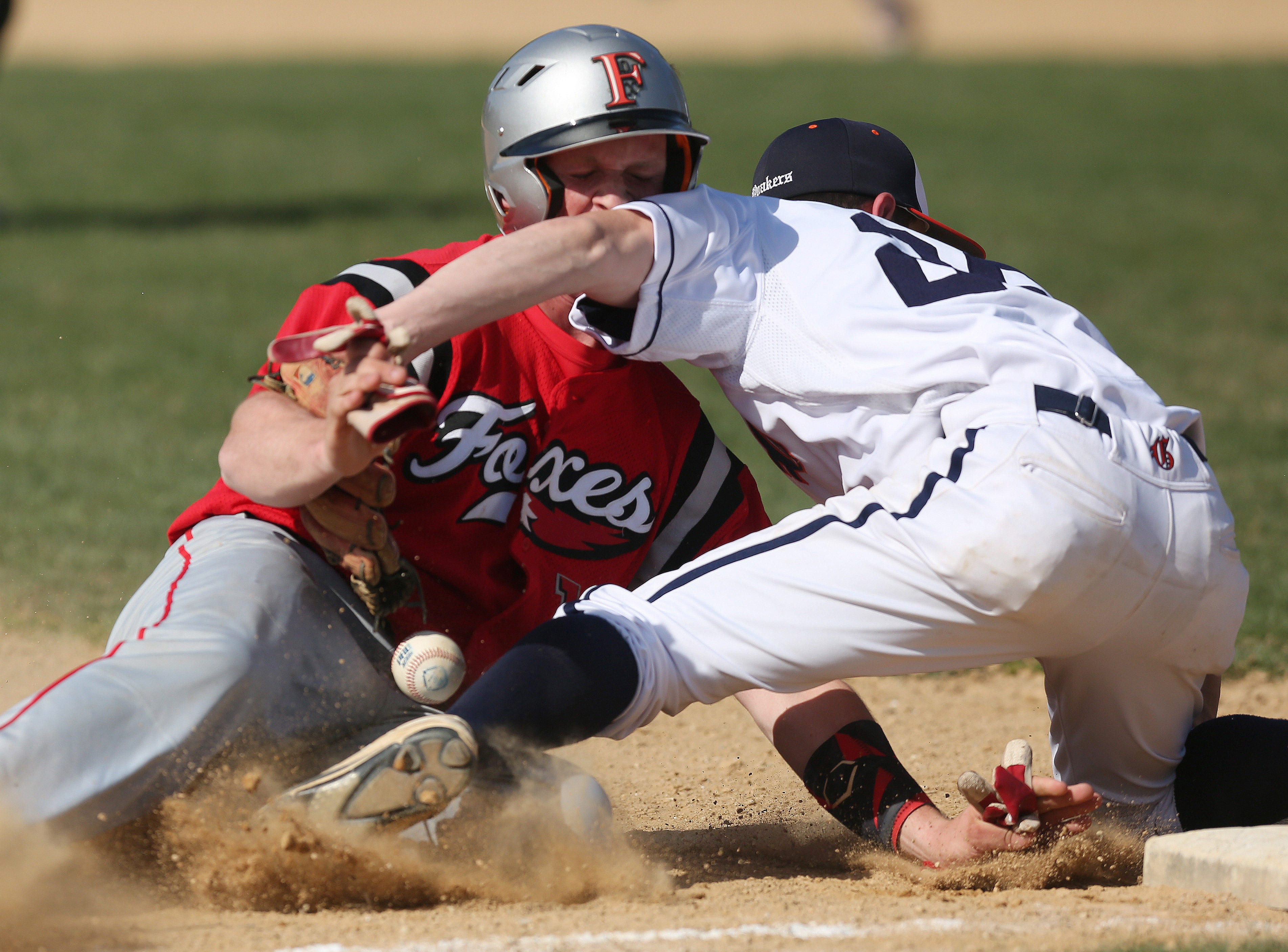 Fox Lane's Thomas O'Sullivan (19) slides safe into third as ball gets away from Greely third baseman Jacob Small (26) during baseball action at Horace Greely High School in Chappaqua May 1, 2018. Fox Lane won the game 9-8.