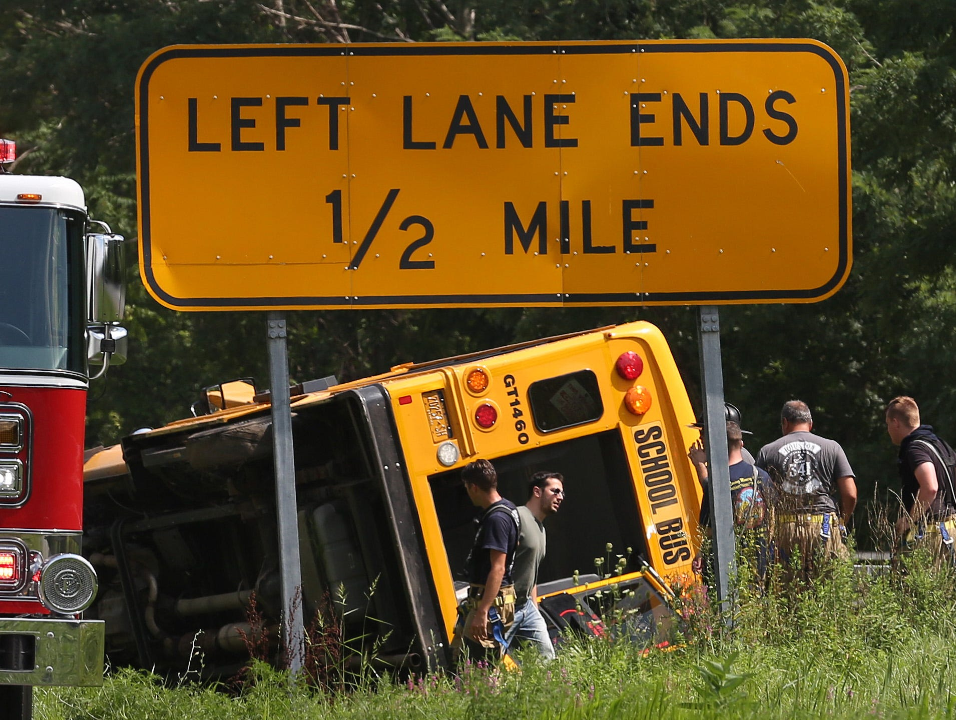 Firefighters work at the scene of a school bus rollover on the Hutchinson River Parkway at Manhattanville Road in Purchase Aug. 14, 2018. There were no injuries.