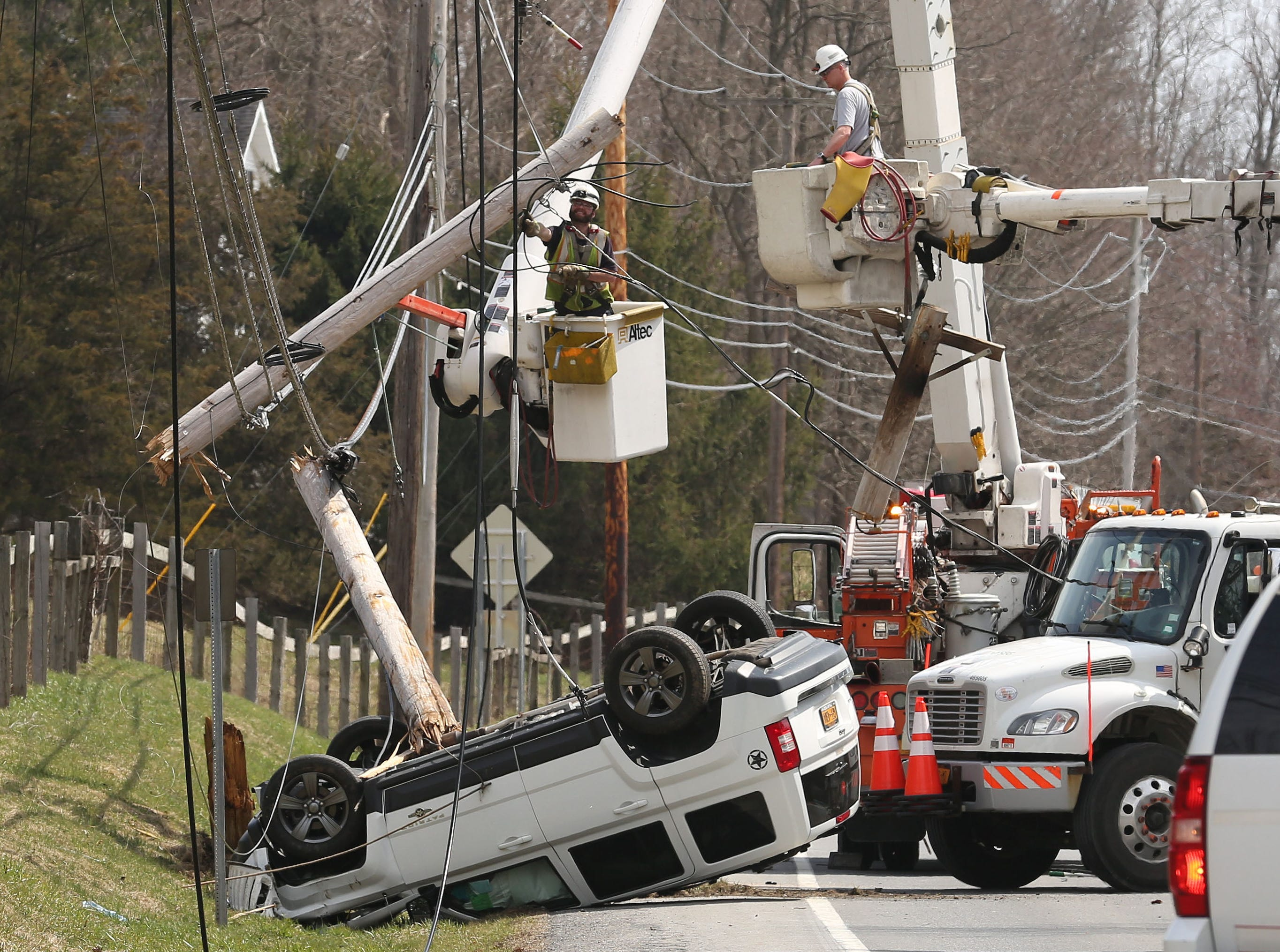 NYSEG utility crews work to repair damaged poles after a car rolled over on Route 22 in Patterson April 13, 2018. The driver of the car was able to escape with only minor injuries. Route 22 was closed in both directions from Route 311 to Havilland Hollow Road.