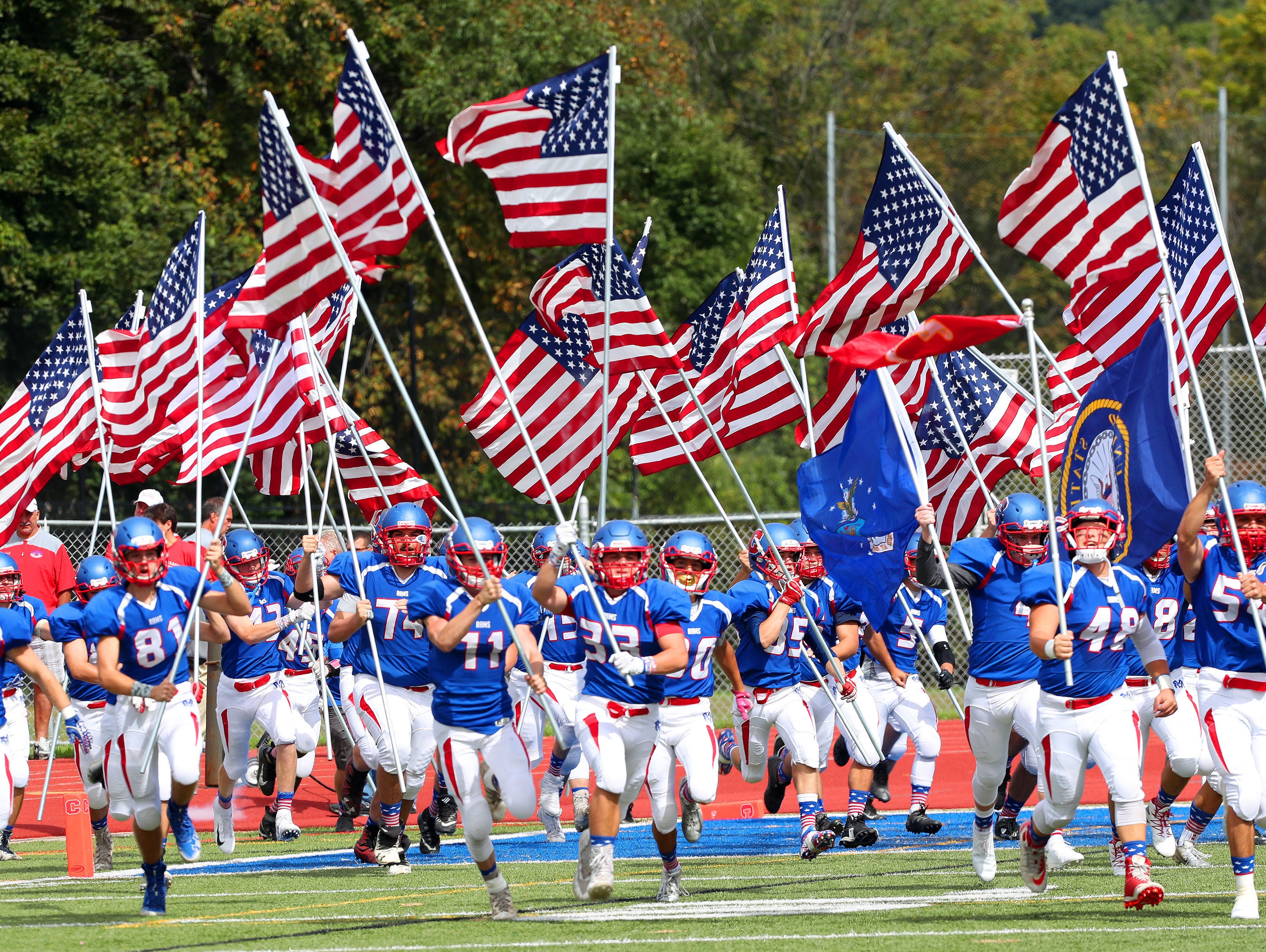 The Carmel football team runs onto the field carrying American flags prior to the start of the game against North Rockland  at Carmel High School Sept. 22, 2018.