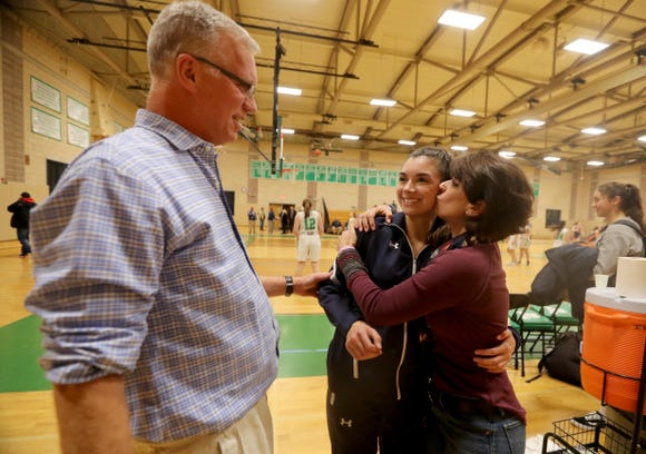Don Hamlin, coach of the Briarcliff High School varsity girls basketball team, watches as his daughter Kacey, who plays on the team, gets a kiss from his wife Denise, who is the team's scorekeeper after Briarcliff defeated Irvington 52-43 at Irvington High School Dec. 12, 2018.
