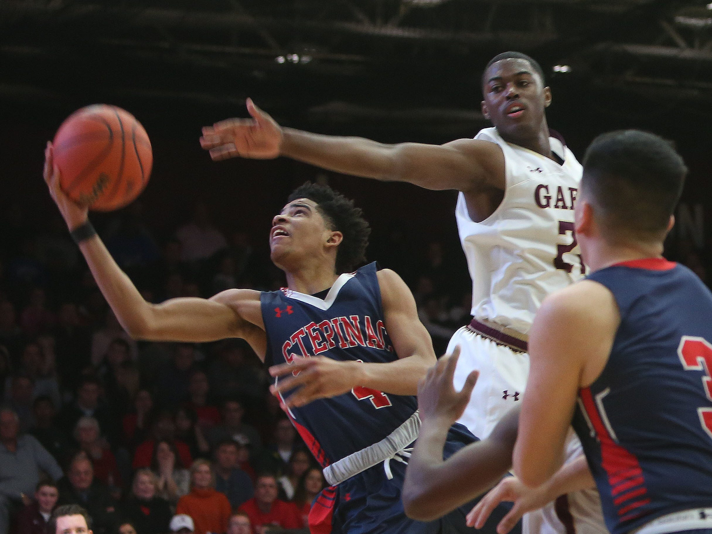 Stepinac's R.J. Davis (4) drives to the basket in front of Iona's Josh Alexander (21) during boys basketball action at Iona College in New Rochelle Feb. 3, 2018. Iona won the game 75-67.