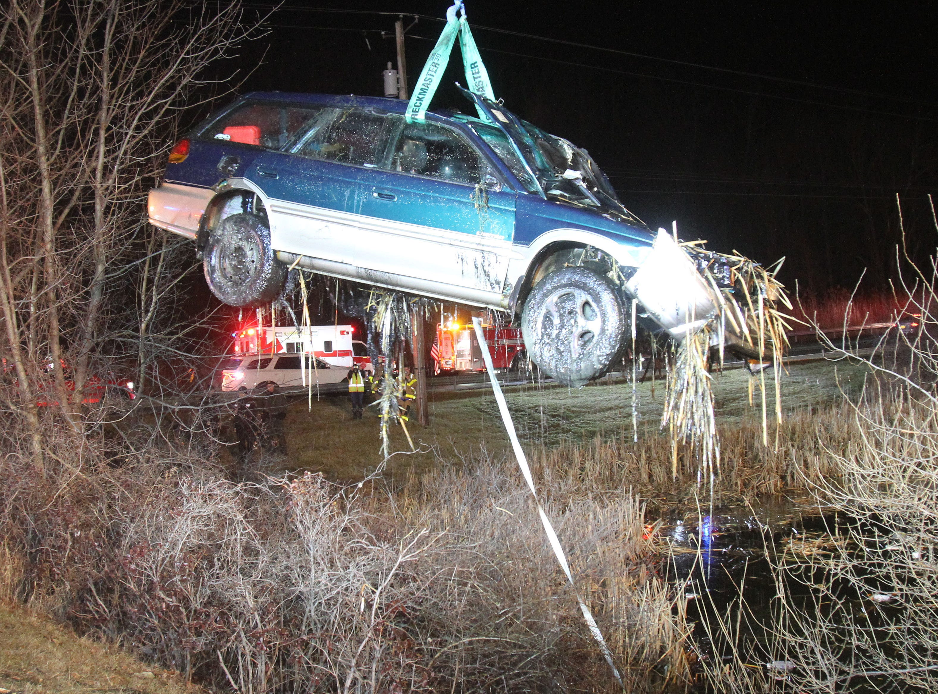 A crew from Lisi's Towing and Recovery lifts a Subaru wagon out of a pond at the intersection of Route 22 and Doansburg Road in the town of Southeast  early Friday morning Feb. 22, 2018. The driver was transported to Danbury Hospital with minor injuries.