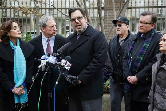 Peter Katsikis, center, along with other sexual assault victims and their attorneys hold a news conference in front of Rockefeller University Hospital in New York, Tuesday, Dec. 11, 2018. Former patients who say they were molested by a physician at the hospital, the late Dr. Reginald Archibald of Pelham, NY, want to know what happened to photos that they say were taken while the abuse was occurring.