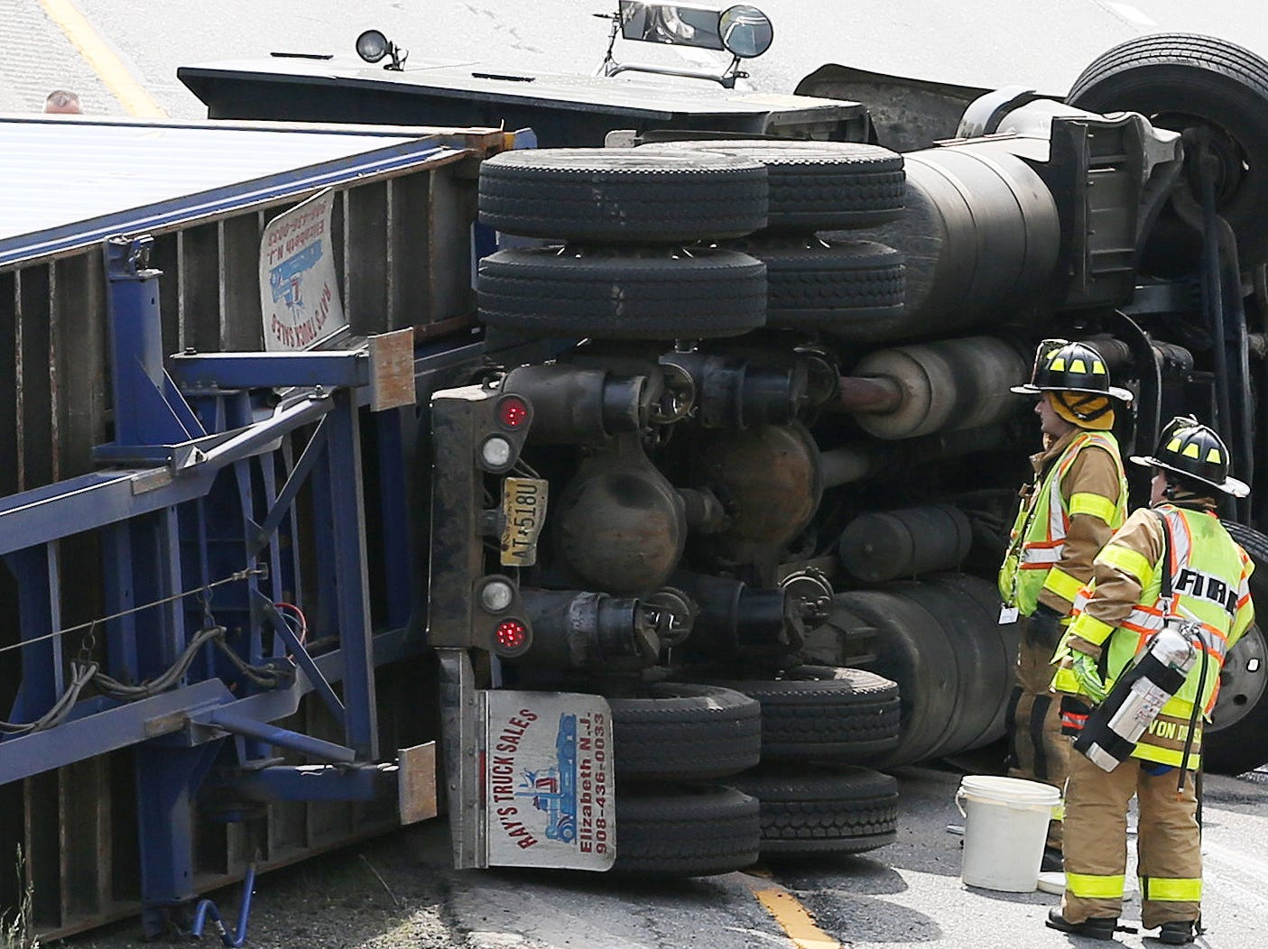 Brewster firefighters check for leaking fuel at the scene of  tractor trailer rollover on eastbound I-84 at the intersection with I-684 in the town of Southeast June 8, 2018. The injured truck driver was transported to Danbury Hospital following the crash.