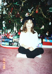 Kerri Dinsmore, 7, sits in front of her family's Christmas tree in early 1999 in Washingtonville, New York, after surviving emergency brain surgery on Christmas Day 1998.