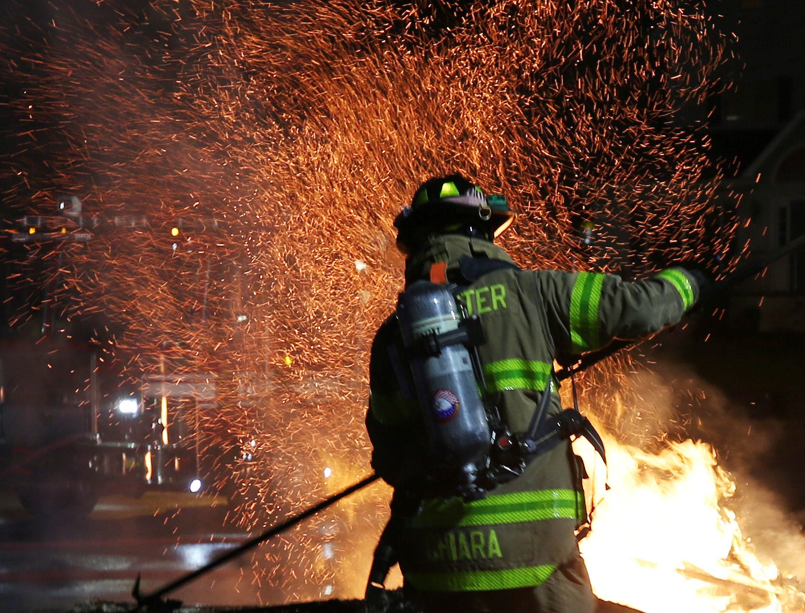 Brewster firefighter Matt Chiara pulls apart a burning structure that was used as a demonstration, as Brewster firefighters showed the public their skills during fire prevention week at Brewster fire headquarters Oct. 14, 2018.
