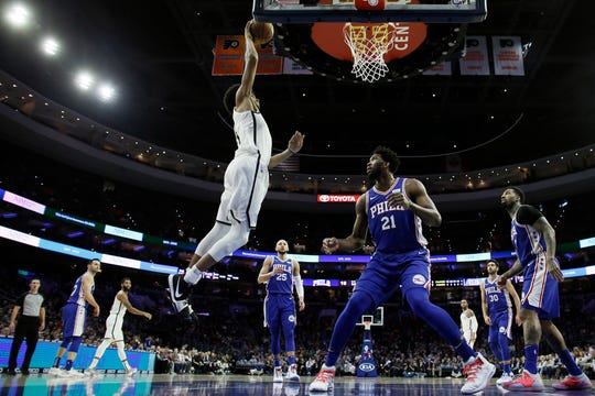 Brooklyn Nets' Jarrett Allen, left, goes up for a dunk as Philadelphia 76ers' Joel Embiid looks on during the first half of an NBA basketball game, Wednesday, Dec. 12, 2018, in Philadelphia. (AP Photo/Matt Slocum)