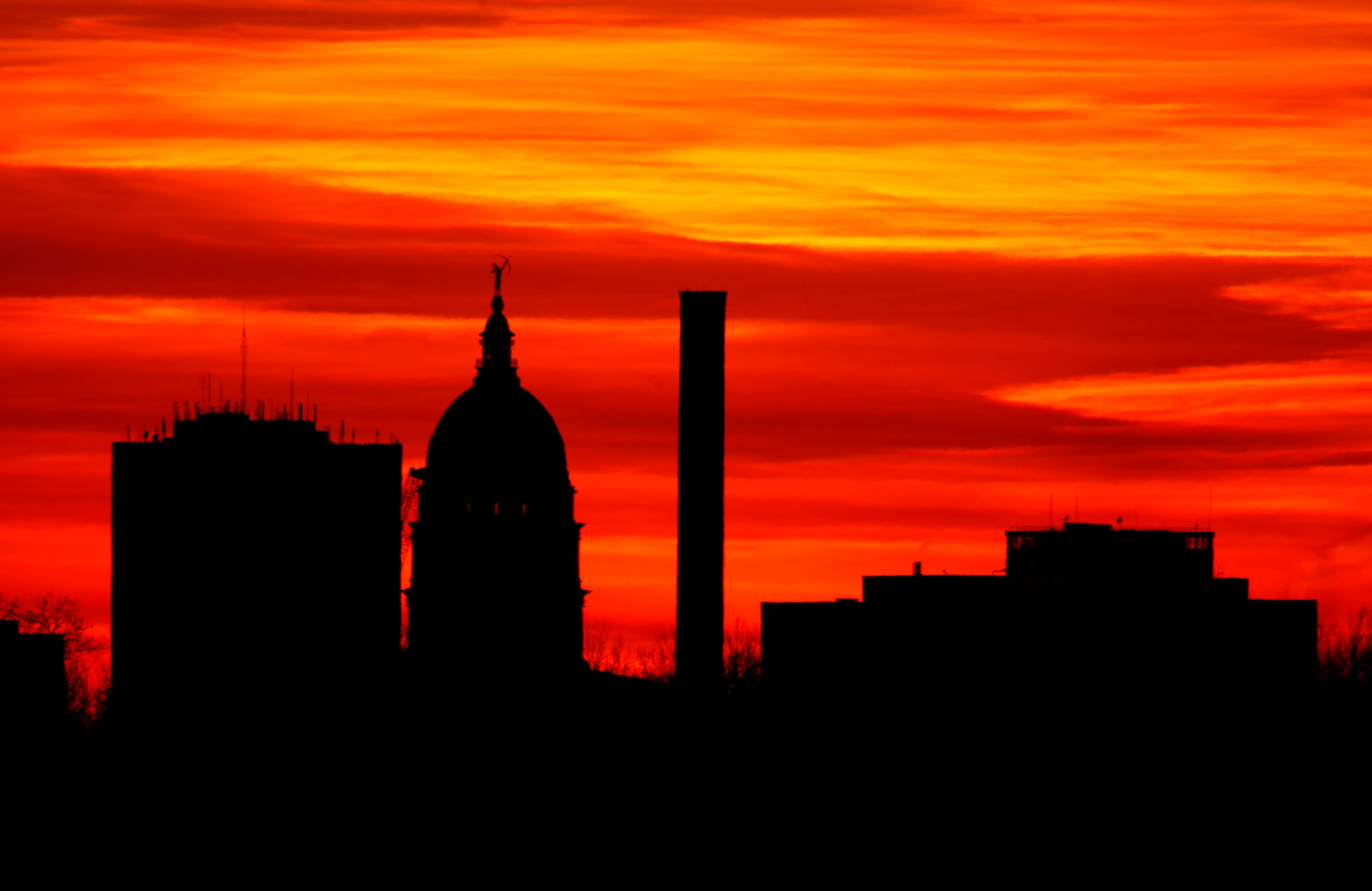 The sun sets behind the Statehouse in downtown Topeka, Kan