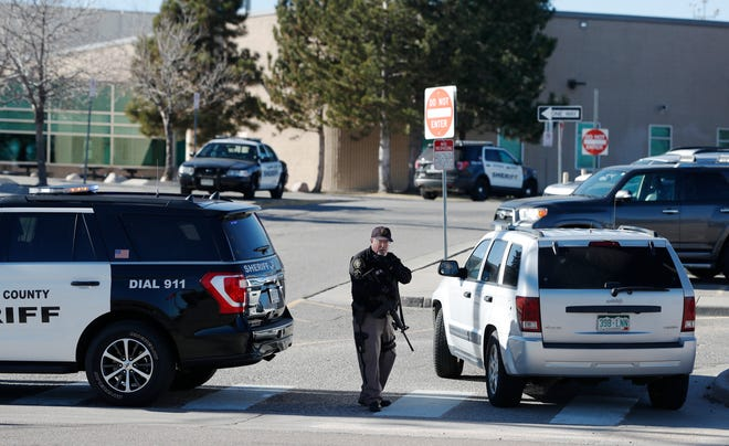 A member of the Jefferson County, Colo., Sheriffs Department stands guard outside the main driveway to Columbine High School Thursday, Dec. 13, 2018, in Littleton, Colo. Students were kept inside the building as a large police response was summoned because a caller claimed to have placed explosive devices in the school and was hiding outside with a weapon. The call was determined to be false. (AP Photo/David Zalubowski)
