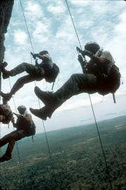 "Competitors rappelling 700 feet from Itan Peak in Borneo during the 2000 edition of ""Eco-Challenge."""
