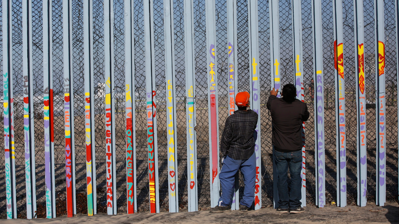Men look through the U.S. border wall, into San Diego, California, from the beach in Tijuana, Mexico, Dec. 11, 2018.