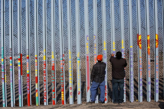 Men look through the U.S. border wall, into San Diego, California, from the beach in Tijuana, Mexico, Dec. 11, 2018.