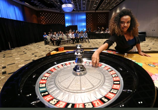 As others wait their turn, Konjo Moges spins a gaming wheel as part of her interview during a job fair put on by the new owner of the Borgata Hotel Casino & Spa for a casino complex that's under construction in Maryland, Wednesday, Aug. 9, 2016, in Atlantic City. MGM says it is seeking hundreds of workers to staff the casino and lounges at MGM National Harbor, which is under development in Prince George's County, Maryland. (AP Photo/Mel Evans) ORG XMIT: NJME107
