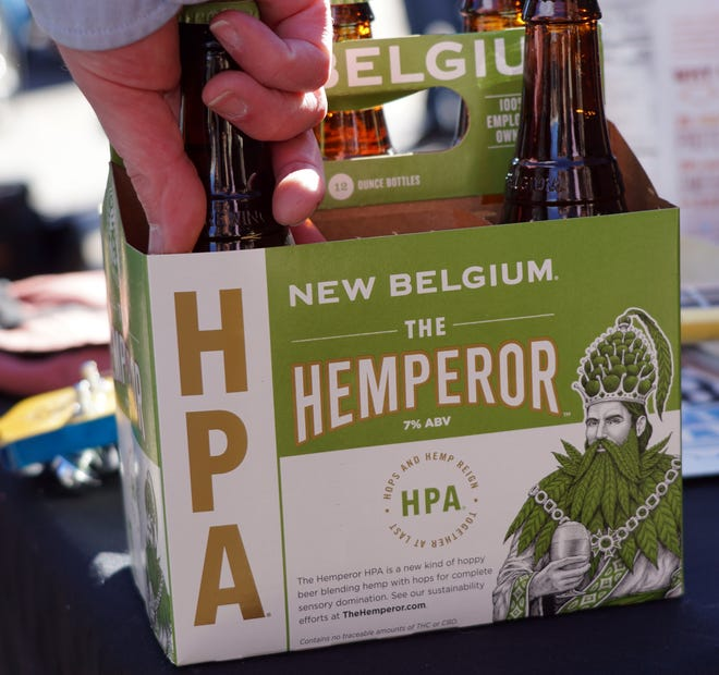 "A participant at a Denver news conference pulls a bottle of New Belgium Brewing's ""The Hemperor HPA"" beer out of a carton. The beer is brewed with hemp seeds and stems, and contains no marijuana. Hemp and hops are close cousins, and enthusiasts love the ""dank"" smell and taste of this beer, which brewers say is just the start of hemp-related products if President Donald Trump signs the Farm Bill and expands hemp farming and use across the country."