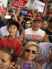 In this file picture from 2017, Cesar Sayoc, far right in red hat, is seen as President Donald Trump speaks during a campaign rally at the AeroMod International hangar at Orlando Melbourne International Airport on February 18, 2017 in Melbourne, Fla. Mr