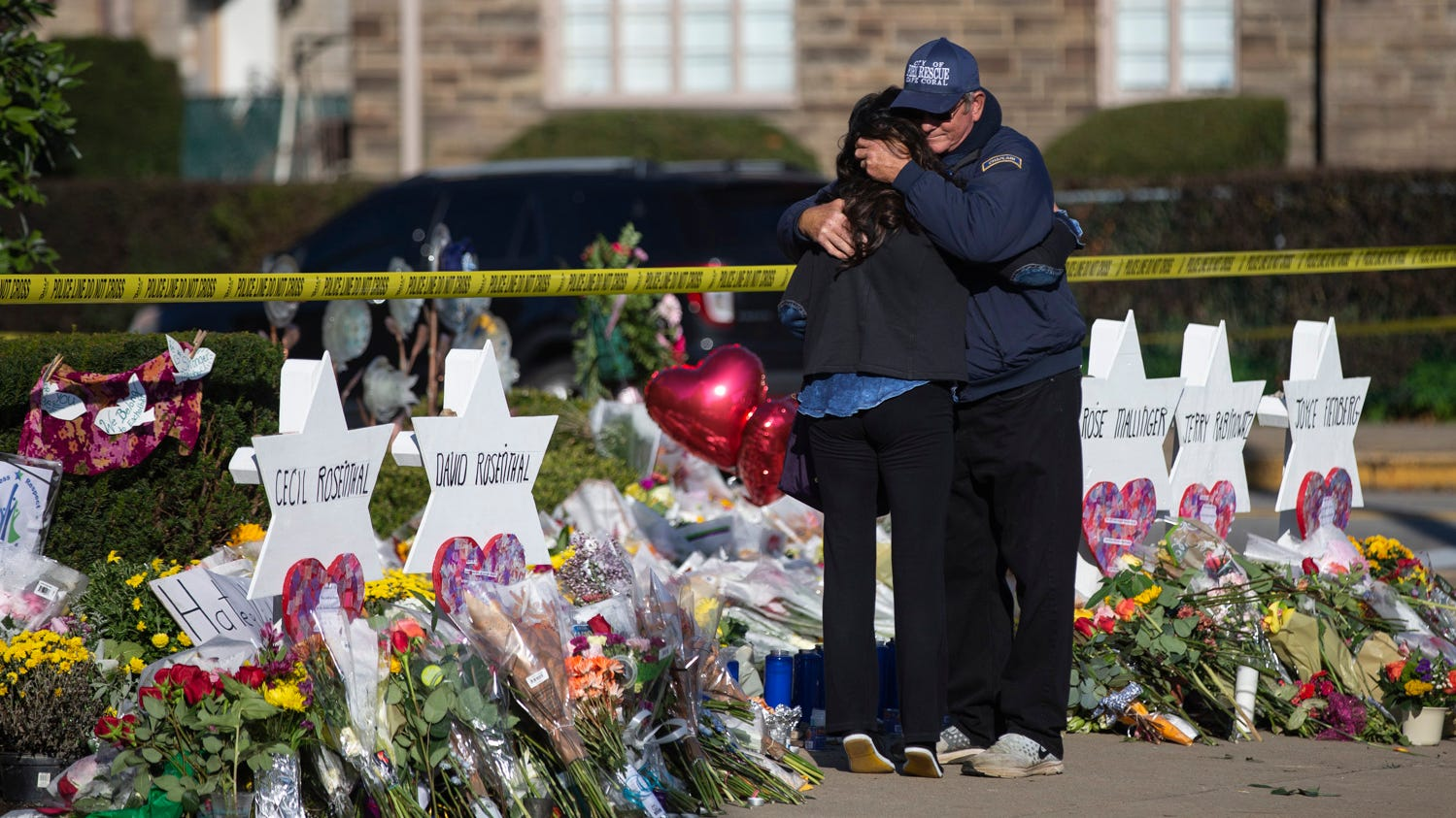 "Florida native and chaplain Bob Ossler, right, hugs Julianne Statnick as she visits a tribute to shooting victims along Shady Avenue in Pittsburgh, Pennsylvania on Tuesday morning. ""I grew up here,"" Statnick said. ""I was in Ireland when this happened so now I'm just here spreading love."""