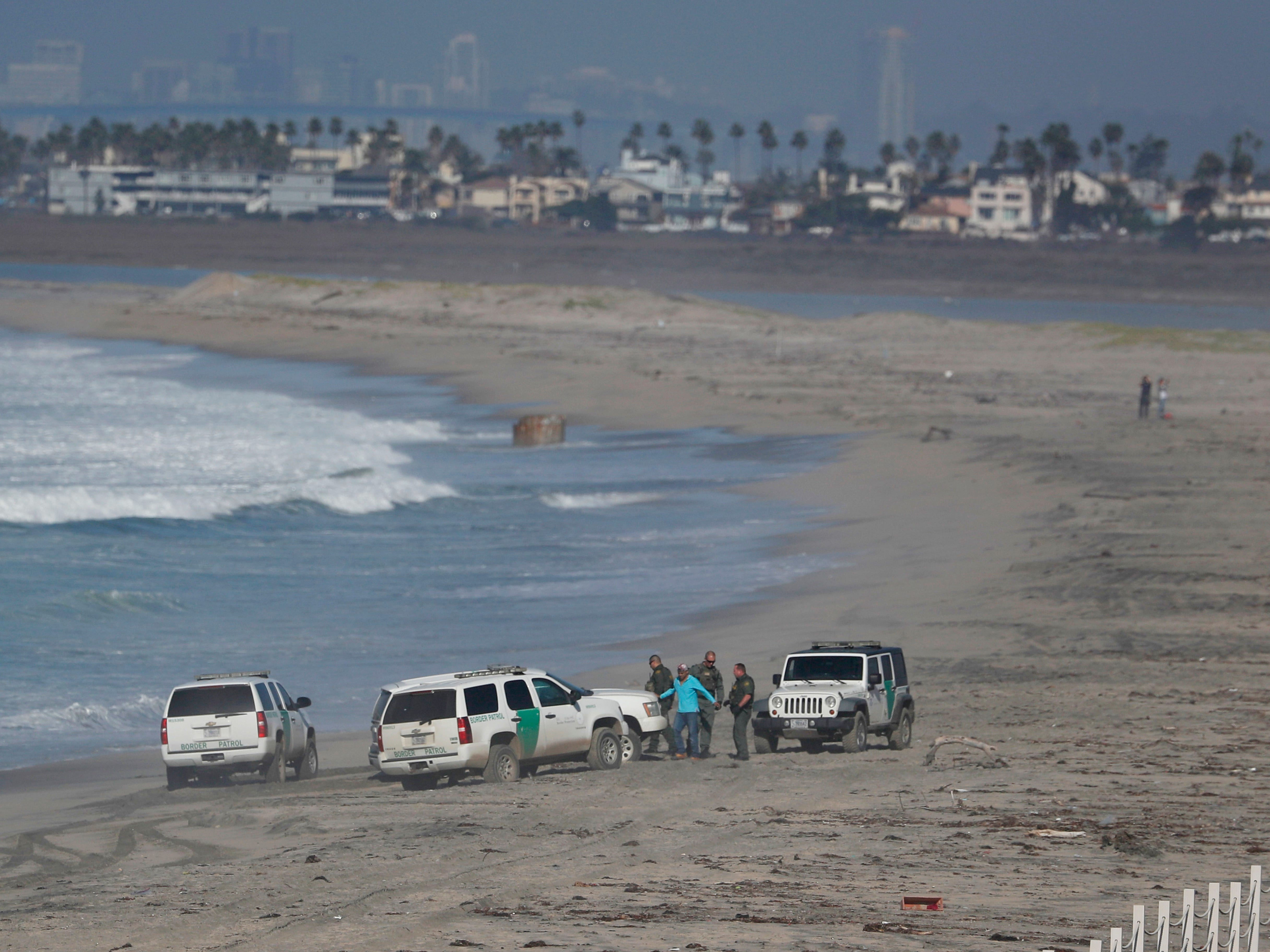 A migrant is taken into custody by U.S. Border Patrol agents after crossing the U.S. border wall into San Diego seen from Tijuana, Mexico on Dec. 11, 2018.