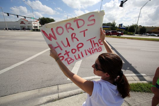 Aimee Galassi holds a sign during a carwash fundraiser for Rebecca Ann Sedwick at the 7-11 on U.S. 98 and Daughtery Road in Lakeland, Fla, Sunday, Sept. 15, 2013. The 12-year-old Lakeland girl was found dead early Tuesday morning at an abandoned cement business. Rebecca committed suicide after being bullied for one and half years.