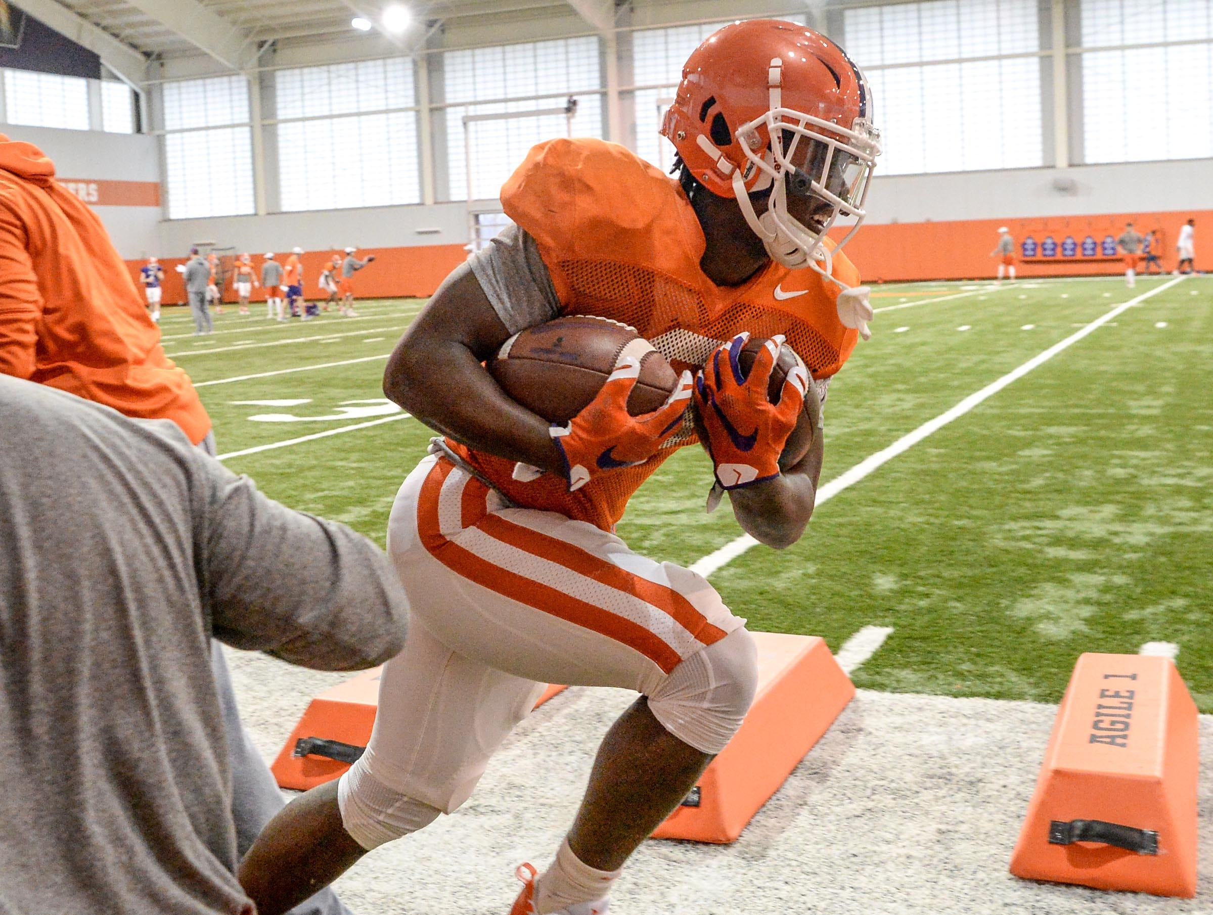 Clemson running back Travis Etienne (9) runs a drill with two footballs during practice for the Cotton Bowl at the Poe Indoor Facility in Clemson Friday, December 14, 2018.