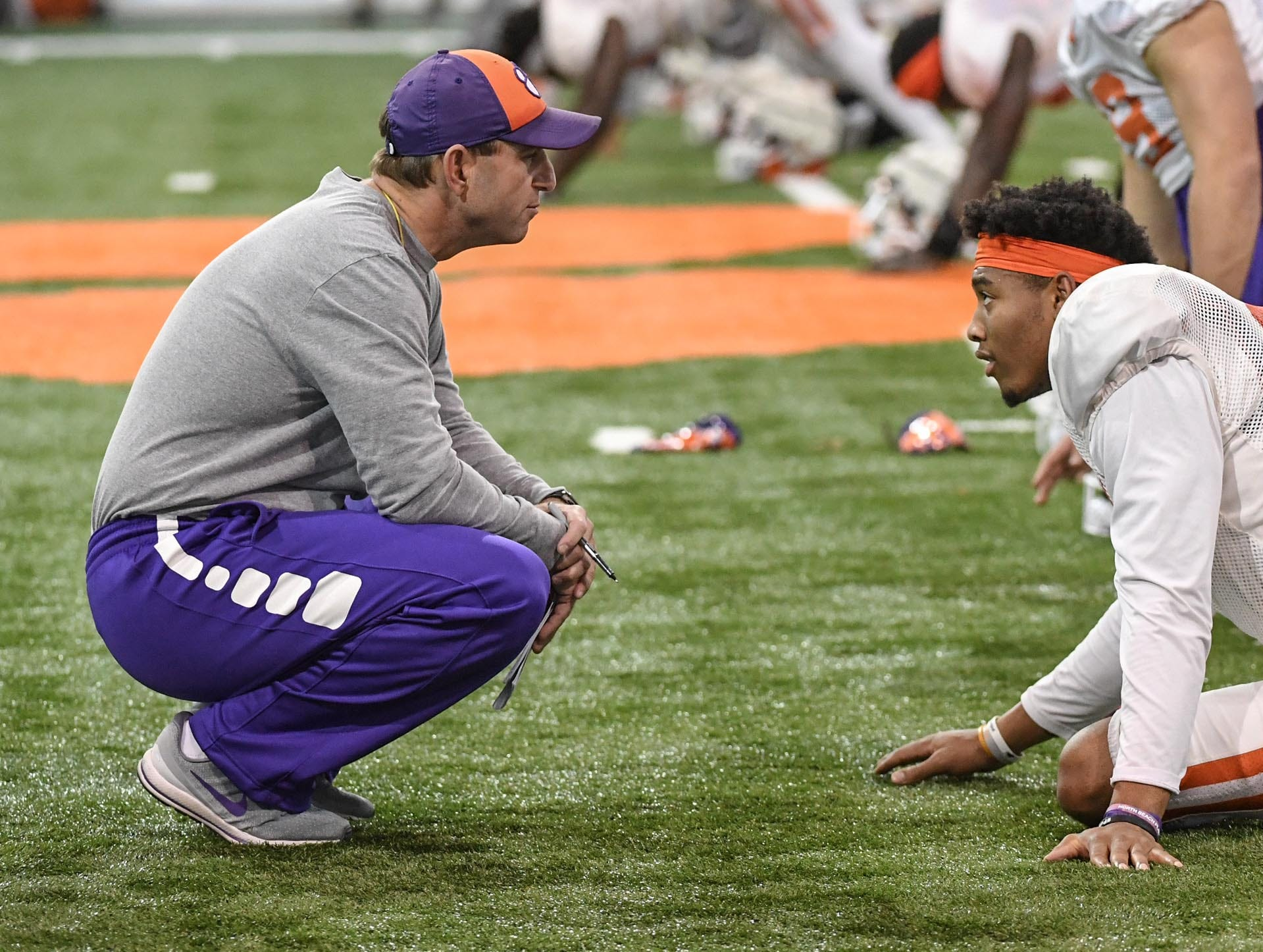 Clemson Head Coach Dabo Swinney, left, listens to Clemson safety Isaiah Simmons (11) stretching during practice for the Cotton Bowl at the Poe Indoor Facility in Clemson Friday, December 14, 2018.