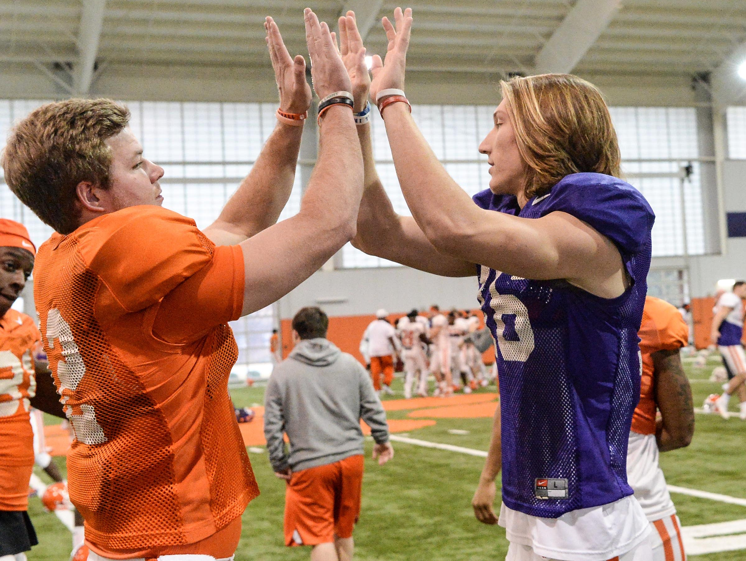 Clemson quarterback Ben Batson, left, greets quarterback Trevor Lawrence (16) during practice for the Cotton Bowl at the Poe Indoor Facility in Clemson Friday, December 14, 2018.