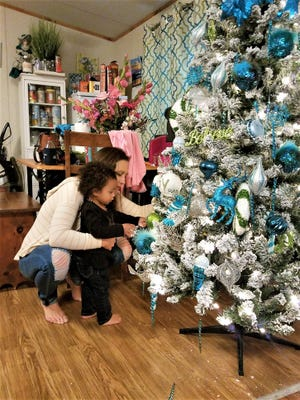 Brittney Metrejean decorates her family's Christmas tree with daughter Brynnlea.
