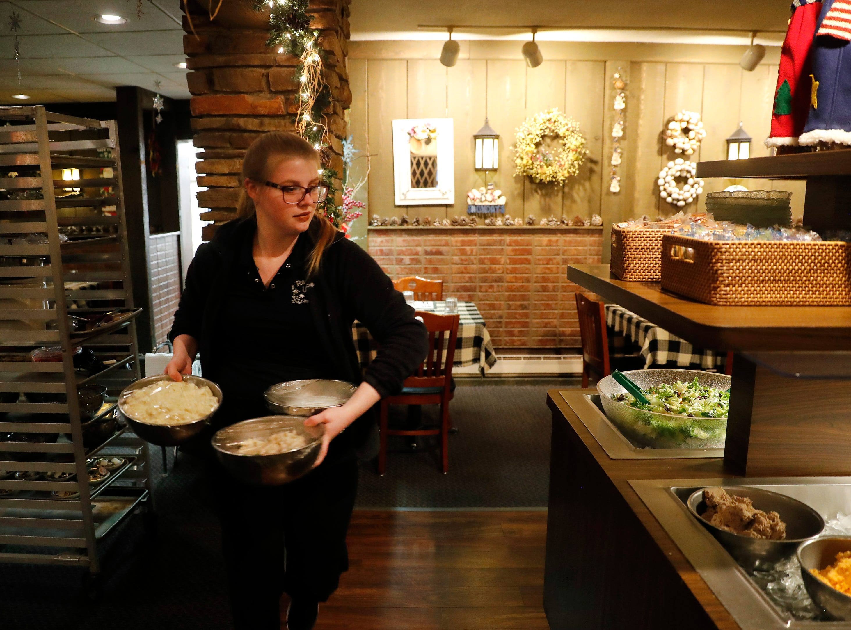 Anita Ditter, an employee at Roepke's Village Inn, prepares the salad bar for service Wednesday, Dec. 12, 2018, in Charlesburg, Wis.